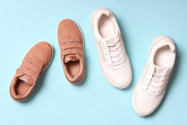 Buty dla dzieci i trampki damskie na kolorowym tle widok z góry