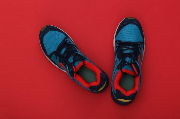 Buty do biegania (trampki) na czerwonym tle. zdrowy tryb życia. widok z góry