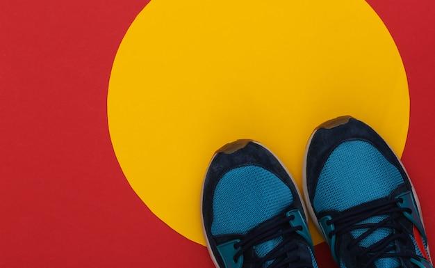 Buty do biegania (trampki) na czerwonym żółtym tle. zdrowy tryb życia. widok z góry