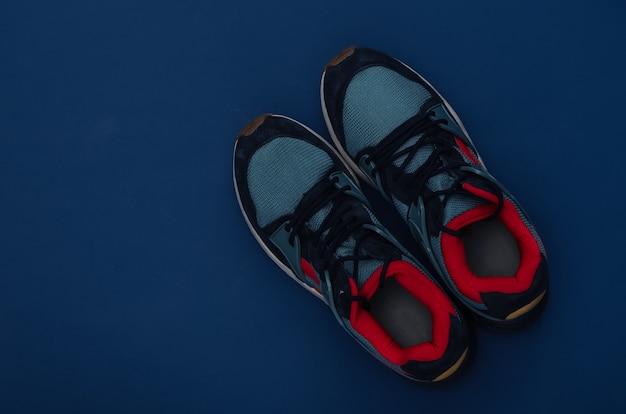 Buty do biegania (trampki) na klasycznym niebieskim tle. zdrowy styl życia, trening fitness. kolor 2020. widok z góry