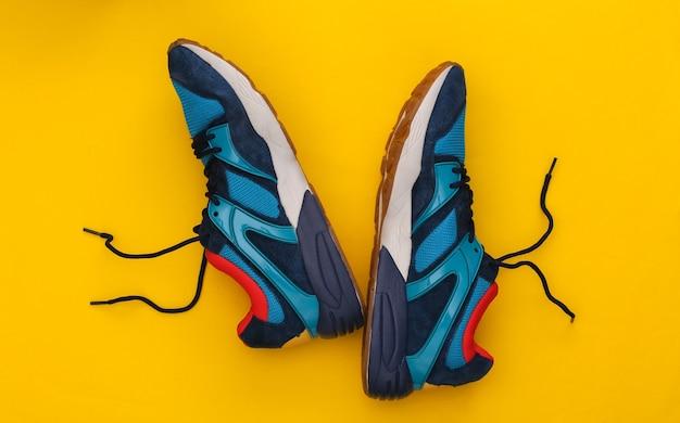 Buty do biegania (trampki) na żółtym tle. zdrowy styl życia, trening fitness. widok z góry