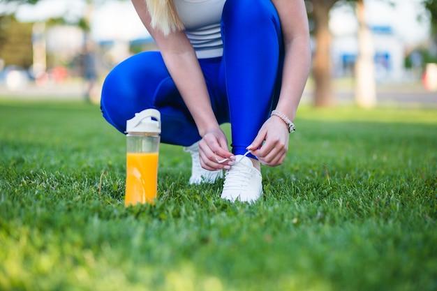 Buty do biegania – zbliżenie kobiety zawiązującej sznurowadła. selektywna koncentracja na rękach.