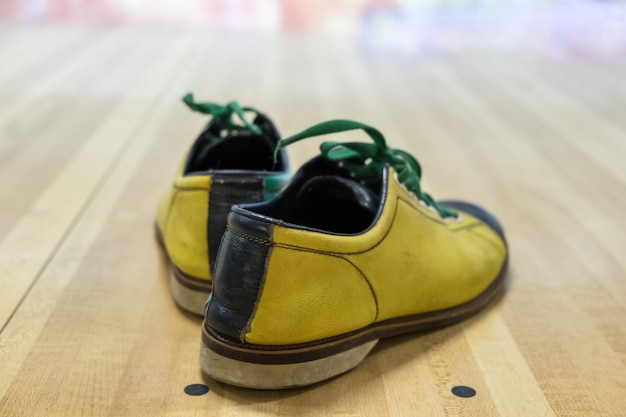 Buty do gry w kręgle żółto-zielone na drewnie parkietowym