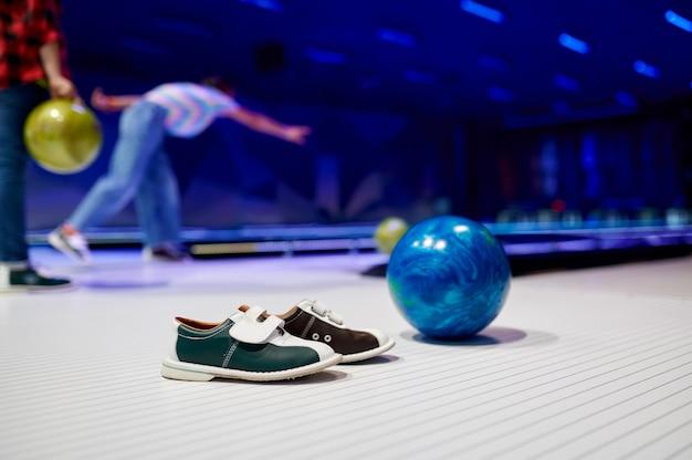 Buty do piłki i domu, dzieci grające w kręgle, koncepcja gry. dzieci przygotowują się do uderzenia. chłopcy i dziewczęta bawią się razem w centrum rozrywki