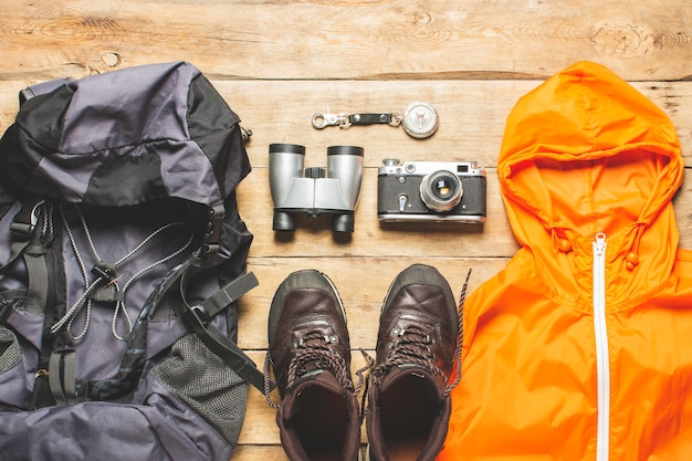 Buty do szlaku, lornetki, akcesoria trekkingowe na drewnianym tle. koncepcja turystyki pieszej, turystyki, obozu, gór, lasu.