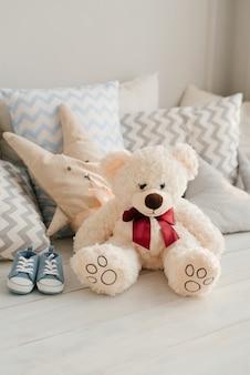 Buty dziecięce dla noworodka. niebieskie trampki dla chłopca w pokoju dziecinnym. miś pluszowy