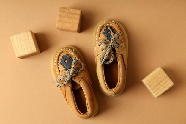 Buty dziecięce i drewniane kostki na beżowym tle.