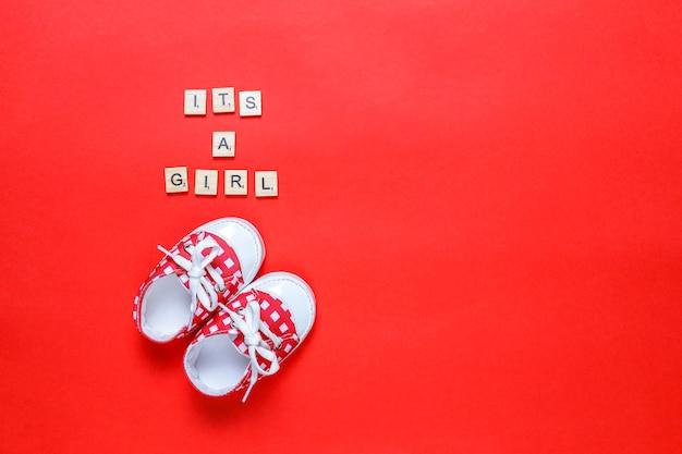 """Buty dziecięce lub dziecięce z napisem """"it's a girl"""" lub """"it's a boy"""", widok z góry."""