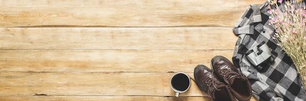 Buty, koszula, polne kwiaty, filiżanka z herbatą, lornetka na drewnianej przestrzeni. pojęcie turystyki pieszej, turystycznej, obozowej, górskiej, leśnej. transparent.