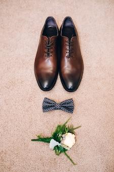 Buty męskie z brązowej skóry. koncepcja ślubu. męskie buty, muszka i boutonniere, widok z góry.