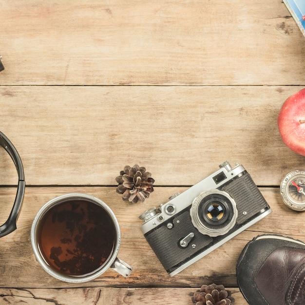 Buty, metalowy kubek z herbatą, kompas i inne atrybuty na wędrówkę po drewnianej powierzchni.