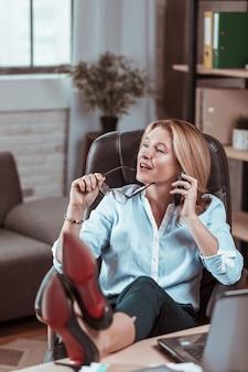 Buty na obcasie. kobieta w czarnych skórzanych butach na wysokim obcasie rozmawia przez telefon