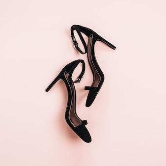 Buty na wysokim obcasie na pastelowym różowym tle. płaski układanie, widok z góry