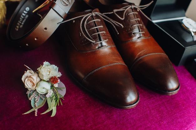 Buty oblubieńca z innymi detalami ślubnymi