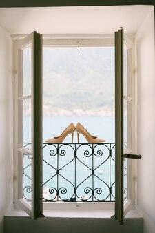 Buty panny młodej na metalowej kratce w otwartym oknie na tle morza.