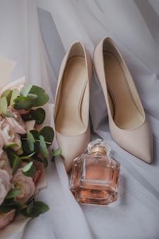Buty panny młodej z bukietem ślubnym i perfumami na welonie. koncepcja ślubu