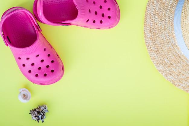 Buty plażowe, kapelusz, muszle na żółtym tle. sandały z muszelką, akcesoria na letnie wakacje.