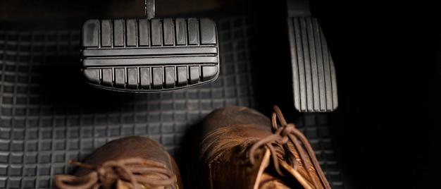 Buty pod hamulcami samochodu spowodują niebezpieczeństwo i wypadki kierowcy.