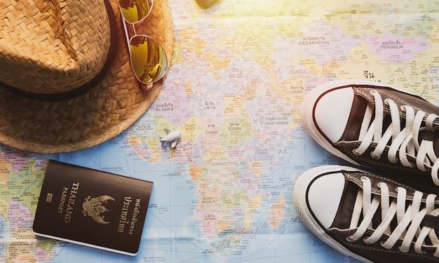 Buty, samolot, słomkowy kapelusz i paszport na mapie z efektem świetlnym słońca