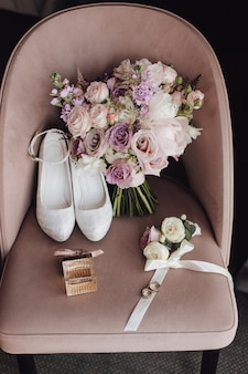 Buty ślubne, bukiet ślubny wykonany z ciemnoróżowych i fioletowych kwiatów na krześle