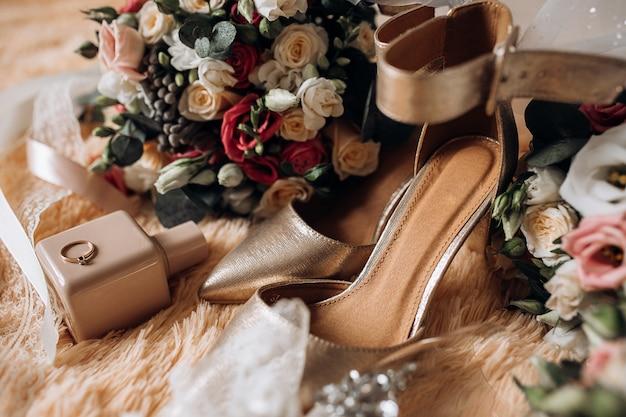 Buty ślubne dla panny młodej, bukiety ślubne, perfumy, cenny pierścionek zaręczynowy z kamieniem szlachetnym