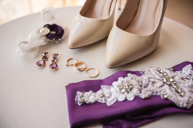 Buty ślubne na wysokich obcasach w pobliżu obrączek ślubnych, biżuterii i pasa do pończoch.