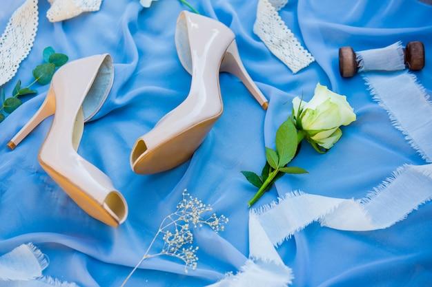 Buty ślubne obuwie. akcesoria ślubne panny młodej. fotografia panna młoda buty na błękitnym tle.
