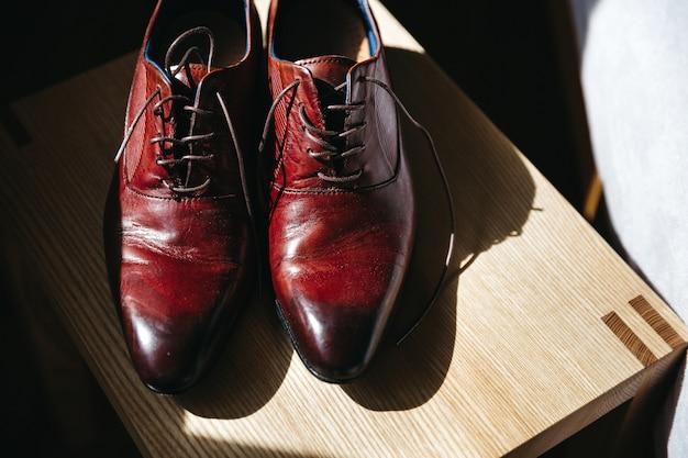 Buty ślubne pana młodego stoją na stołku