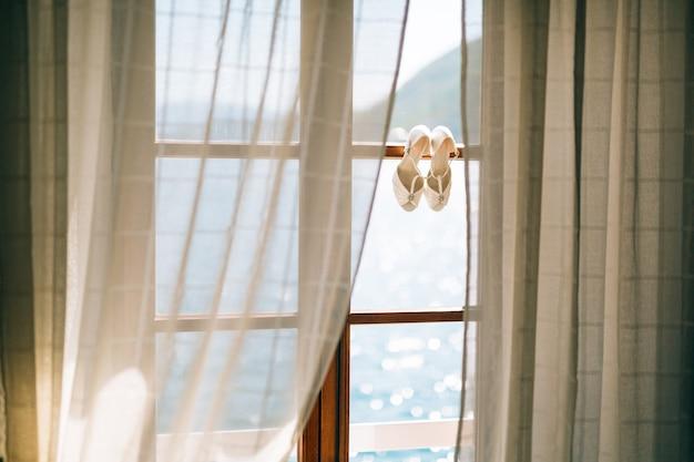 Buty ślubne panny młodej w oknie