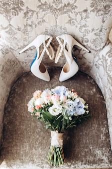 Buty ślubne panny młodej z bukietem piwonii i innych kwiatów.