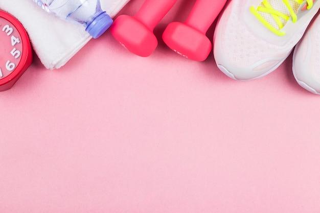 Buty sportowe, fitness hantle, na różowym tle. różne narzędzia sportowe