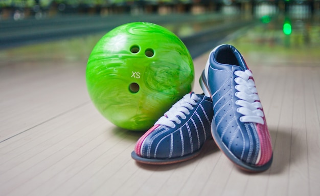 Buty sportowe i zielona piłka na podłodze w kręgielni