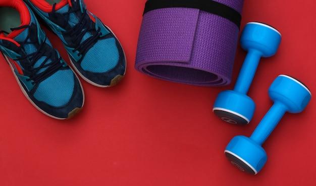 Buty sportowe (trampki) i niebieskie hantle, mata fitness na czerwonym tle. zdrowy styl życia, trening fitness. widok z góry