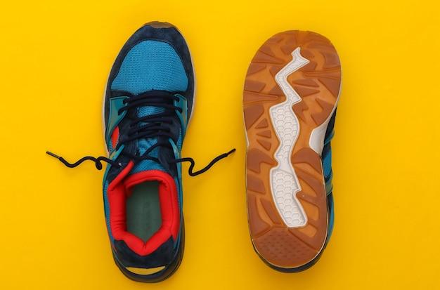 Buty sportowe (trampki) na żółtym tle. zdrowy styl życia, trening fitness. widok z góry