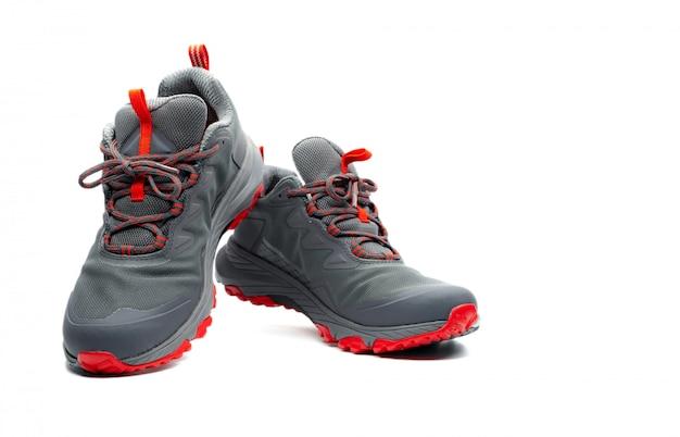 Buty trekkingowe mężczyzn na białym tle. szaro-czerwone buty turystyczne. obuwie ochronne do wspinaczki. sprzęt przygodowy. lekkie gumowe buty trekkingowe z bezpieczną podeszwą.