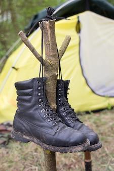 Buty trekkingowe wiszą na gałęzi do wyschnięcia na tle namiotu turystycznego. obraz koncepcyjny.