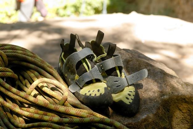 Buty turystyczne i liny na tle ogniska. relacja z podróży w stylu życia. letnie wakacje na świeżym powietrzu. kobieta i mężczyzna buty trekkingowe. miłość do koncepcji podróży. sprzęt outdoorowy, przedmioty przygodowe.