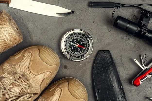 Buty turystyczne, kompas i nóż. sprzęt turystyczny na zewnątrz