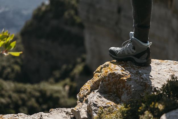 Buty turystyczne stąpające po małej skale z rozmytym tłem krajobrazu w słoneczny dzień miejsca kopiowania
