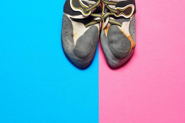 Buty wspinaczkowe na niebieskim i różowym kolorowym tle z miejscem na kopię płasko leżał. widok z góry