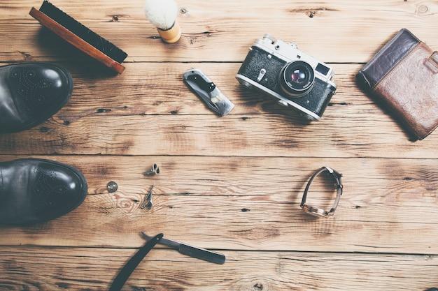Buty zegarek, portfel i aparat na drewnianym