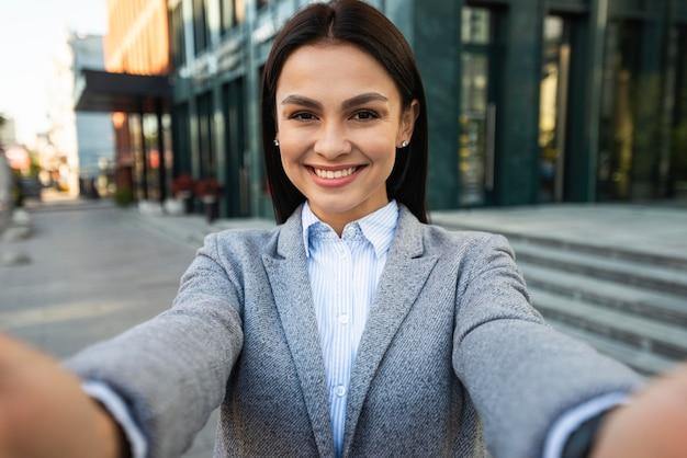 Buźka businesswoman robienia selfie w mieście