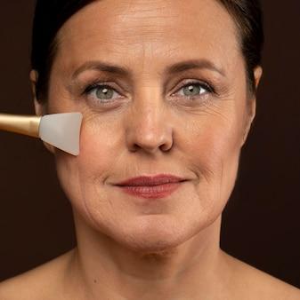 Buźka dojrzała kobieta za pomocą pędzla do twarzy z różowego kwarcu