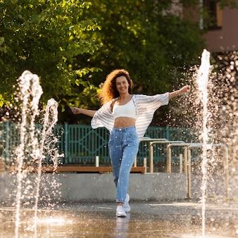 Buźka dziewczyna pozuje otoczona fontanną