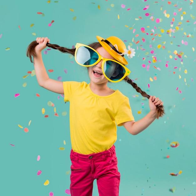 Buźka dziewczyna z konfetti i duże okulary przeciwsłoneczne
