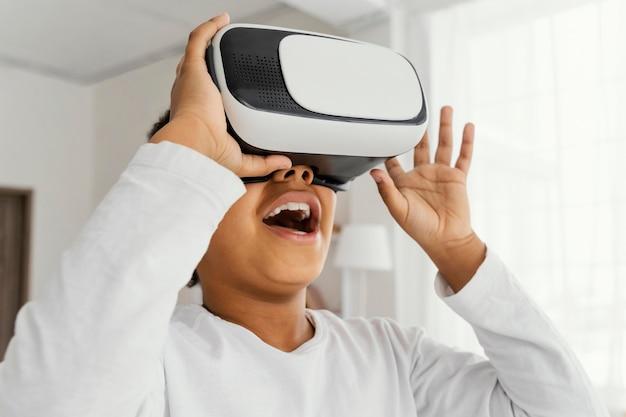 Buźka dziewczynka bawi się w domu z zestawem słuchawkowym wirtualnej rzeczywistości