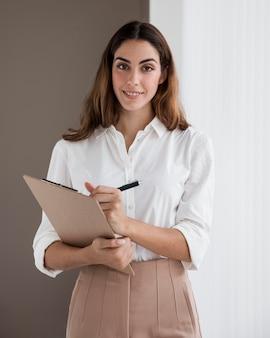 Buźka elegancka bizneswoman trzyma schowek