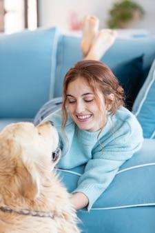 Buźka kobieta na kanapie z psem