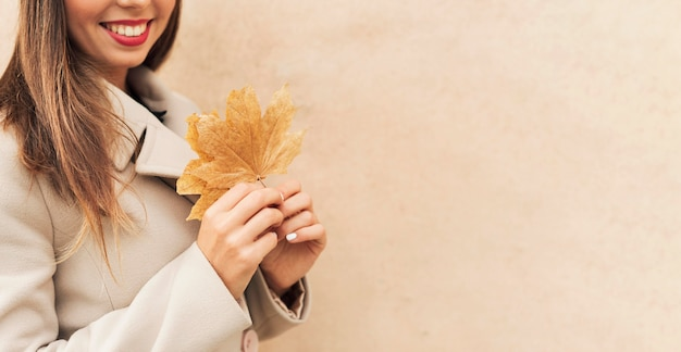 Buźka kobieta trzyma jesienny liść