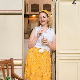 Buźka kobieta trzyma szklankę lemoniady obok przyczepy kempingowej